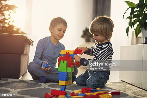 Little boy playing with blocks with little brother