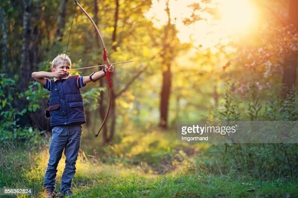 menino brincando com arco na floresta - arco arco e flecha - fotografias e filmes do acervo