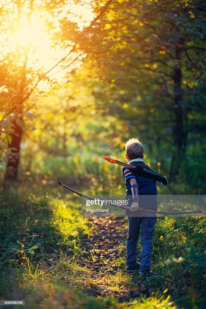 Kleiner Junge spielt mit Bogen im Wald : Stock-Foto