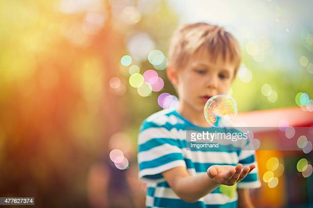 Little boy playing with bubbles at the outdoors kids party
