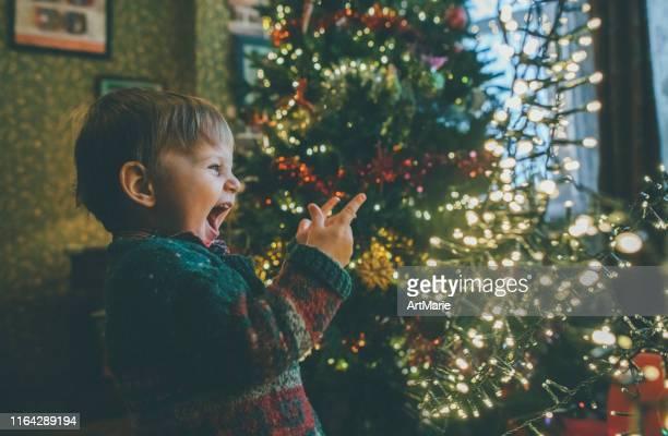 bambino che gioca con le luci di natale a casa - gioia foto e immagini stock