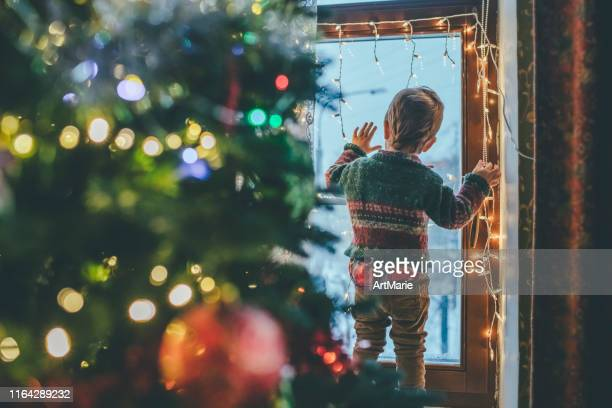 little boy playing with christmas lights at home - waiting stock pictures, royalty-free photos & images