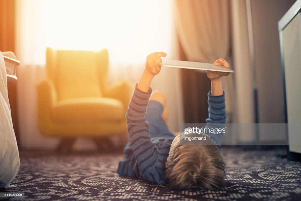 Kleine Jungen spielen mit Digitaltablett auf dem Boden : Stock-Foto