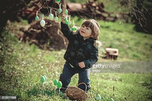 Kleine Jungen spielen mit Ostereier im Freien