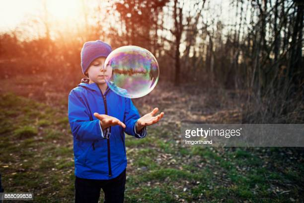 Little boy playing with giant bubble