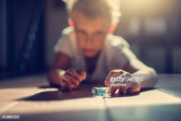 Little boy playing with glass marbles
