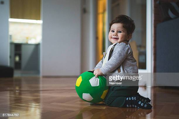 Little boy playing with green ball