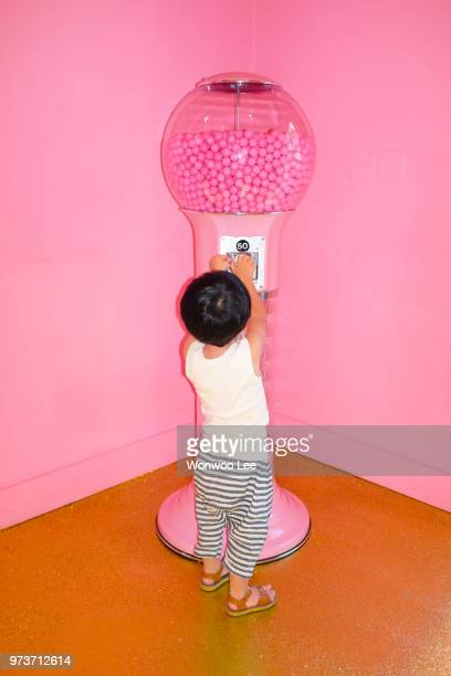 little boy playing with gumball machine - gumball machine stock pictures, royalty-free photos & images