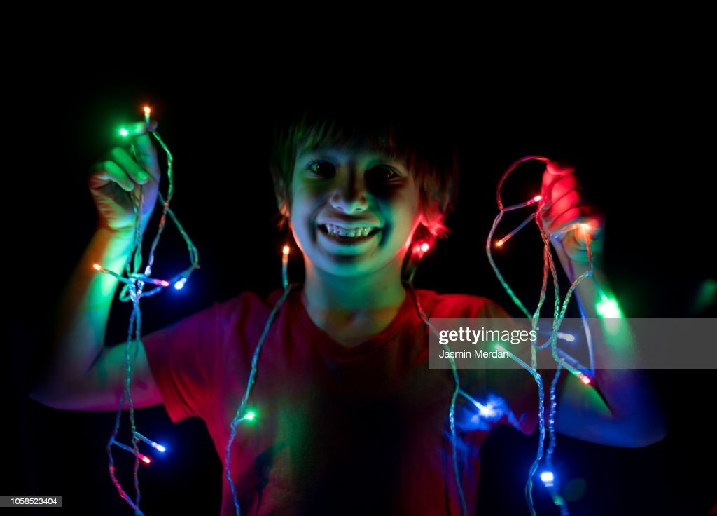 Little Boy Playing With Lights At Nigh