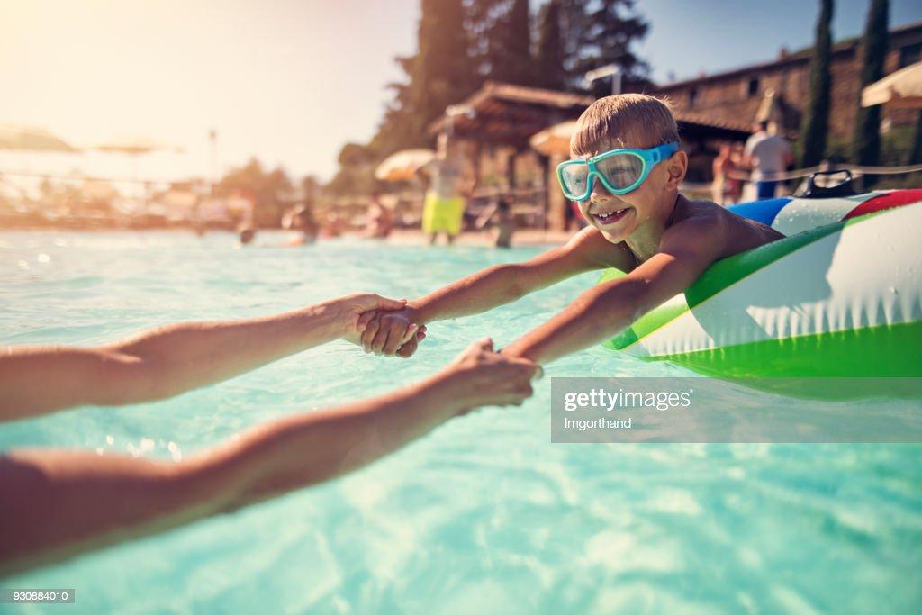 Petit garçon jouant avec la mère dans la piscine : Photo