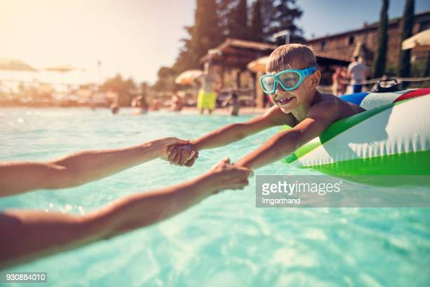 little boy playing with mother in swimming pool - pool stock pictures, royalty-free photos & images