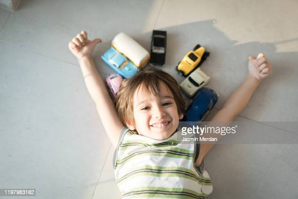 little boy playing with old vintage models of cars - seulement des enfants photos et images de collection