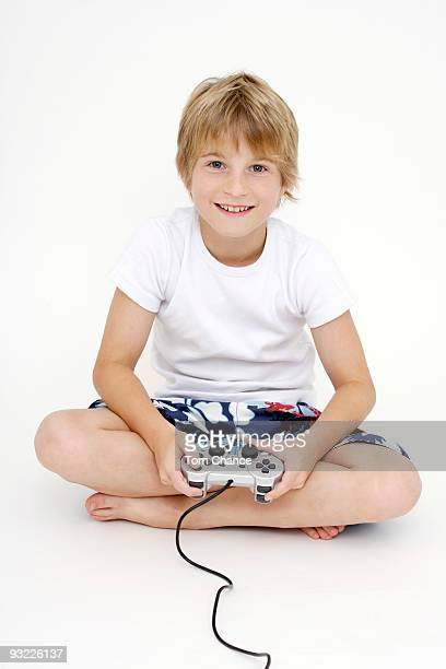 Boy (10-11) playing computer game, smiling, portrait