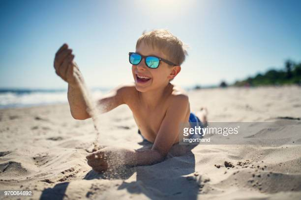 little boy playing with sand on the beach - bambini in spiaggia senza costume foto e immagini stock