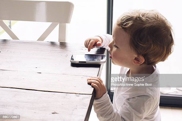 Little boy playing with smartphone left on edge of table