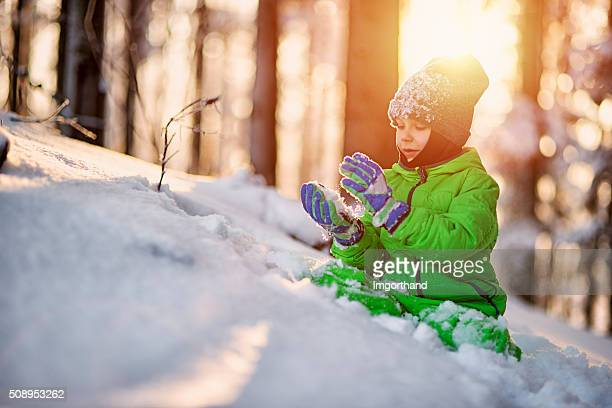 Little boy playing with snow in winter forest