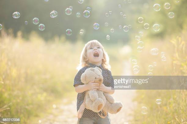 Little boy playing with soap bubbles and bear toy