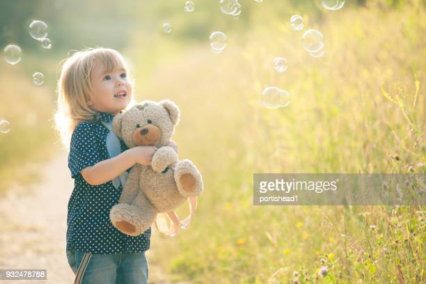 petit garçon jouant avec des bulles de savon et ourson - un seul petit garçon photos et images de collection