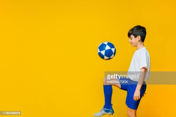 little boy playing with soccer ball on yellow background - sporting term stock pictures, royalty-free photos & images