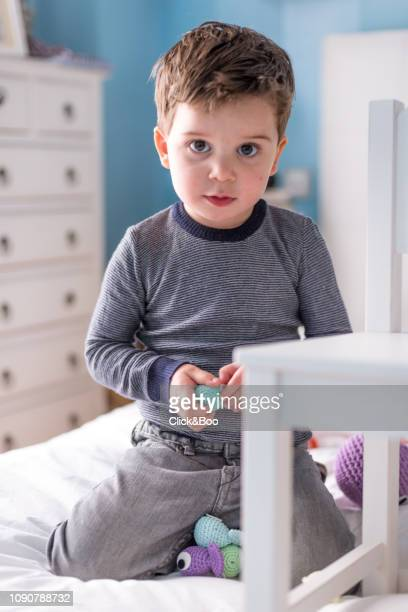 Little boy playing with stuffed animals on a bed