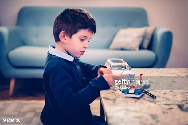 Little boy playing with toy cars indoors