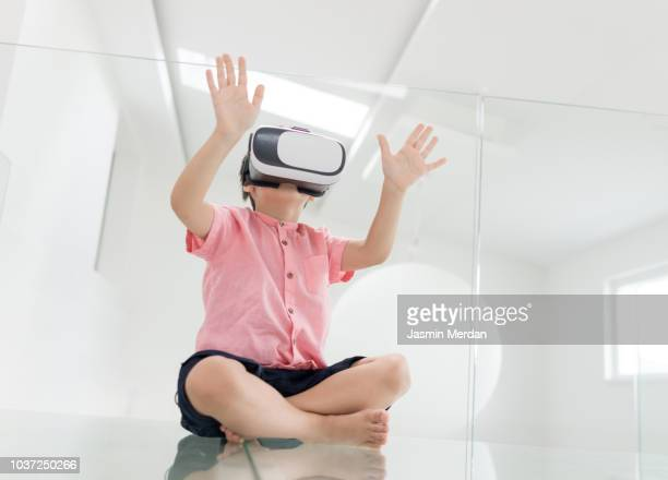 Little boy playing with virtual reality gadget in futuristic room