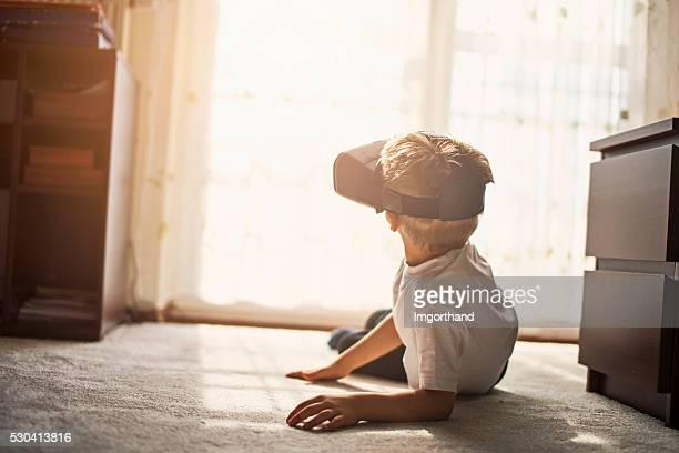 Pequeno Menino a brincar com auscultadores com microfone de realidade virtual