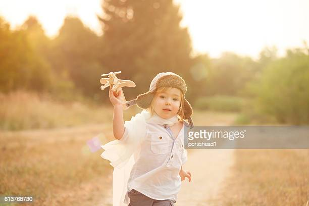 Little boy playing with wooden aircraft in park