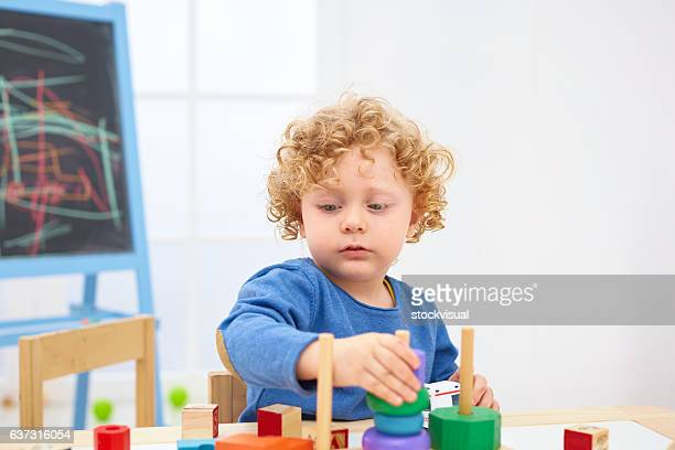 Little boy playing with wooden pyramid at table