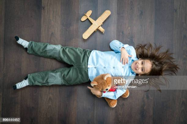 little boy playing with wooden toy airplane - lying on front stock pictures, royalty-free photos & images