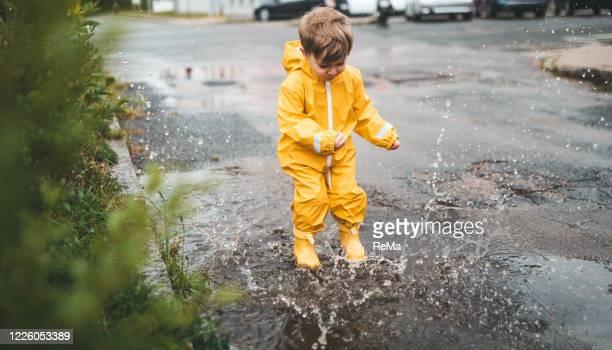 kleiner junge spielt im regen und springt in die wasserlacken - 2 3 jahre stock-fotos und bilder