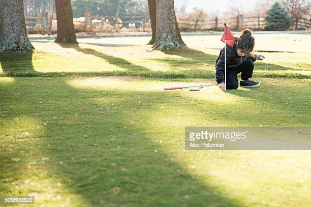 Little boy plays mini-golf at the lawn