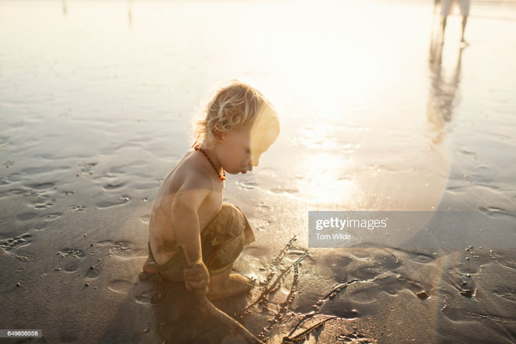 Little boy plays on the beach as the sun sets behind him : Stock Photo