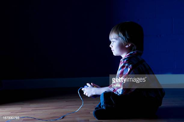 Little boy plays video game in the dark