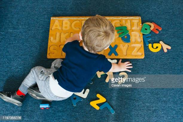 a little boy plays with an alphabet puzzle. - montessori education stock pictures, royalty-free photos & images