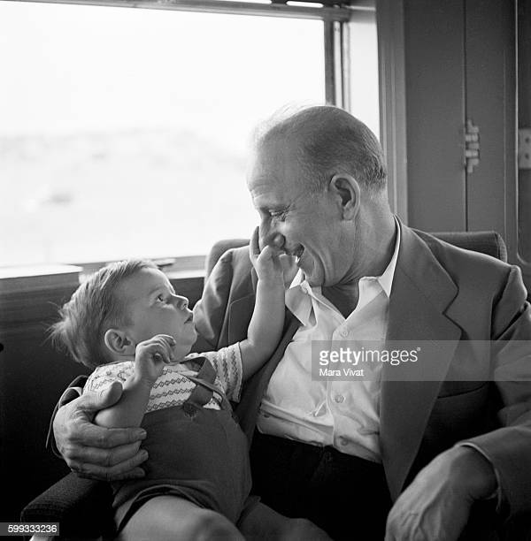 A little boy plays with the nose of comedian Jimmy Durante also known as Schnozzola