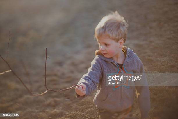 Little boy pointing a stick