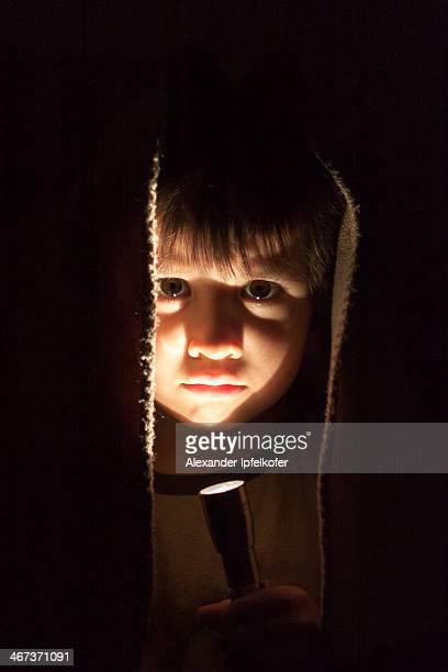 Little boy portrait lit by torchlight