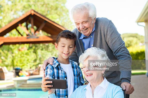 Little boy poses for selfie with grandparents