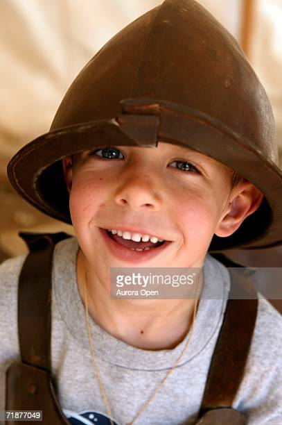 a little boy poses in an old metal helmet. - williamsburg virginia stock pictures, royalty-free photos & images