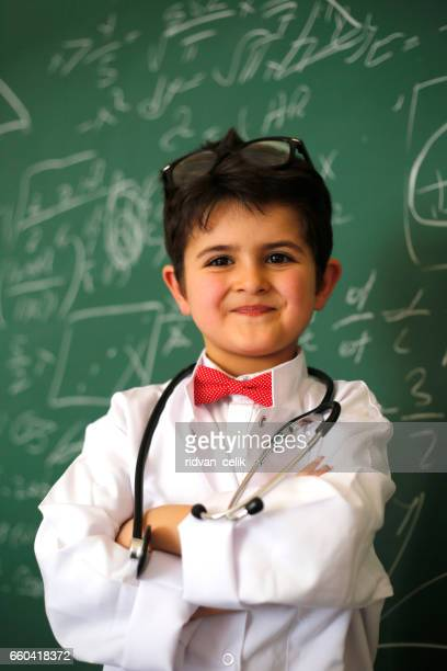 little boy posing before blackboard with mathematic formulas written on - mathematician stock pictures, royalty-free photos & images