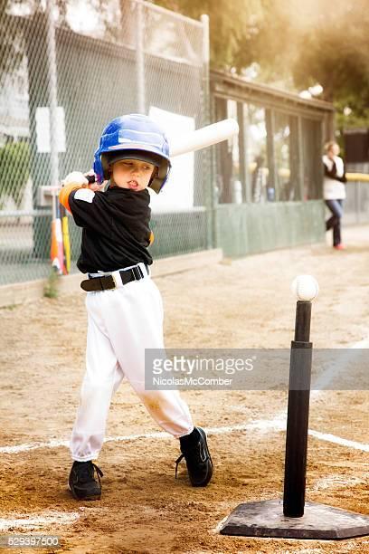 Little boy practicing baseball swing at T-Ball