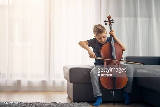 little boy practicing cello at home - practicing stock pictures, royalty-free photos & images
