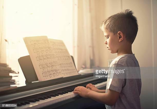 Petit garçon pratiquant un piano numérique.