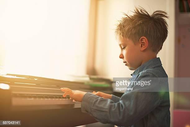 デジタルピアノを練習する少年。