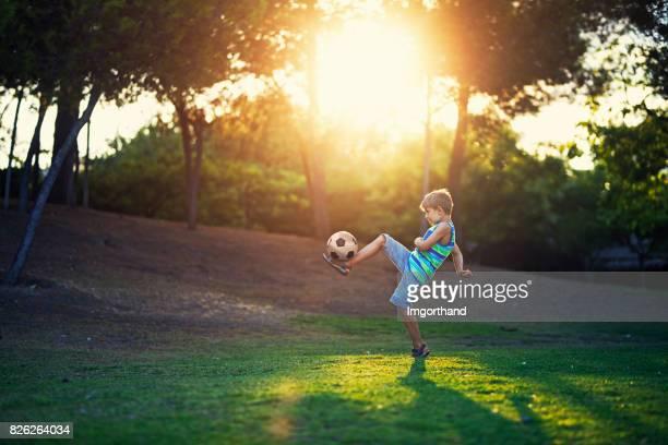 kleine jongen beoefenen voetbal houden ups in het park - football in spain stockfoto's en -beelden