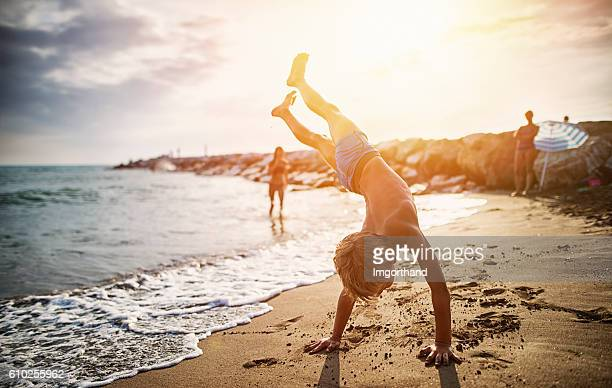 little boy practicing handstand on beach - activiteit bewegen stockfoto's en -beelden
