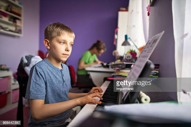 little boy practicing piano - keyboard player stock photos and pictures