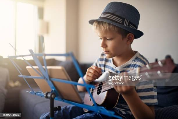 little boy practicing ukulele at home - ukulele stock pictures, royalty-free photos & images