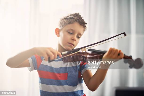 little boy practicing violin at home - violin family stock photos and pictures